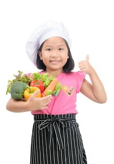 小さな笑顔のシェフは、健康的な、白い背景に隔離された野菜の食品のための親指を与えて