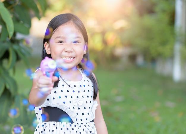 幸せなアジアの女の子、バブルの石鹸を家庭で、健康的な概念を再生