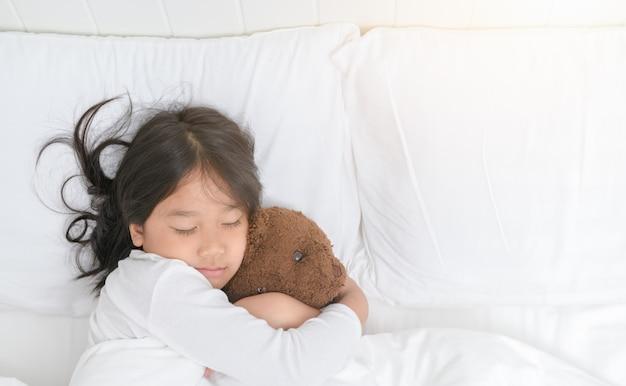 Девушка обнимает плюшевого медведя, когда спит в постели