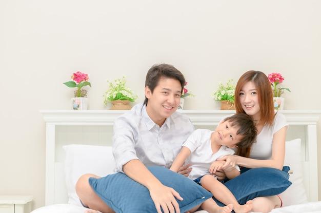 寝室の白いベッドのアジアの幸せな家族