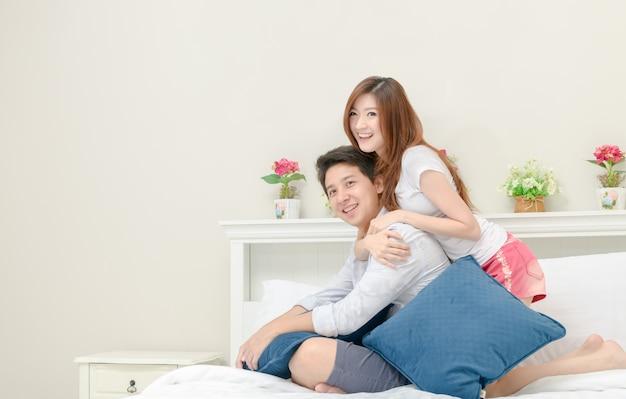 幸せなカップルは笑顔と自宅でベッドに座って