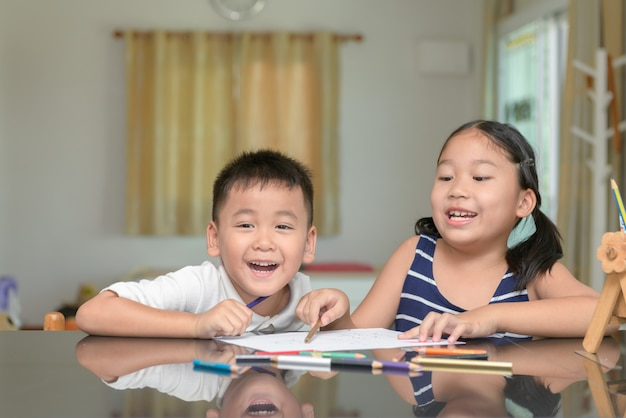 幸せな子供たちがカラフルな鉛筆で絵を描い