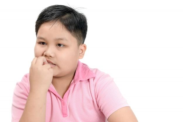 肥えた太った少年を噛む爪