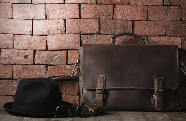 ヴィンテージレザーバッグと帽子、木製テーブル