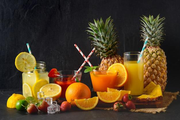 Лимонный, апельсиновый и клубничный сок на черном