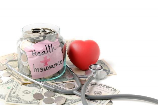 聴診器と紙幣の背景が付いている瓶の中のコイン
