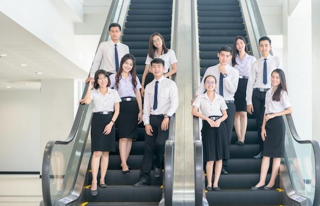 スマートな若い学生たちがエスカレーターで一緒に立っています