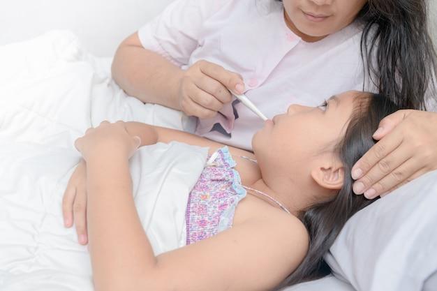 母親は病気の子供の体温を測定します。