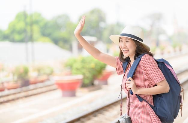 バッグを持つ女性旅行者は友達にこんにちはと言います、