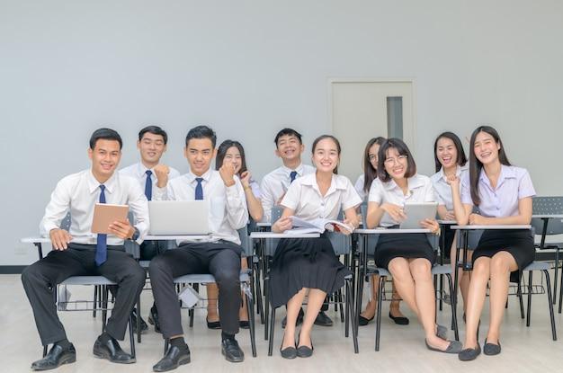 ノートパソコンで作業の制服を着た幸せな学生