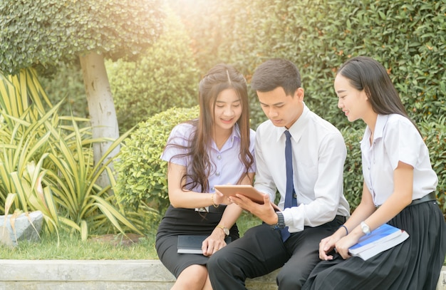 アジアの学生が宿題をするためにタブレットを使う