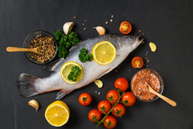 Свежая рыба сибас и ингредиенты для приготовления пищи.