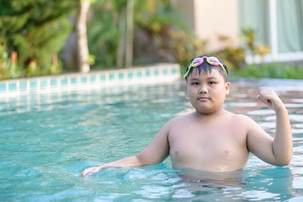 Тучный толстый мальчик показывает мышцы в бассейне