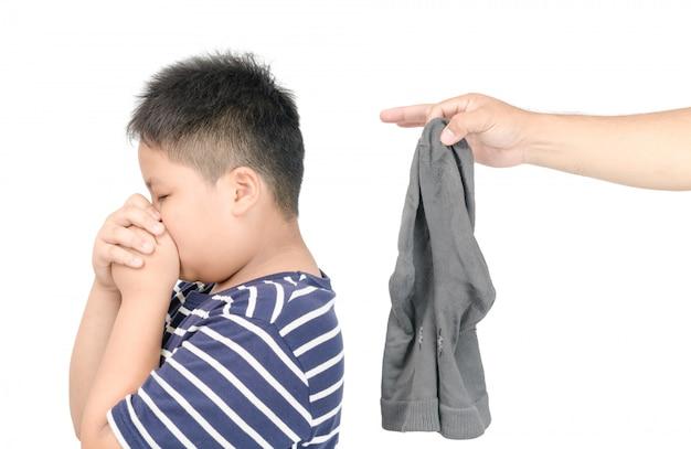 白い背景に、不快な臭いの概念に分離された汚れた臭い靴下を持っている手マン