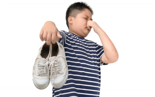 臭い靴のペアを保持しているうんざりした太った少年