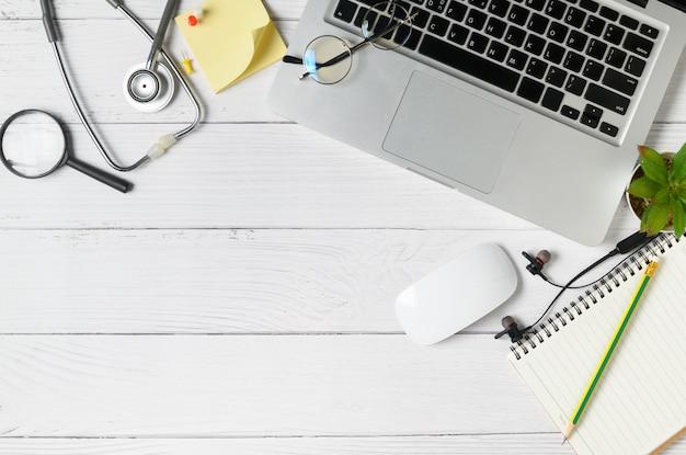 医者の机の大理石のテーブルと聴診器とノート