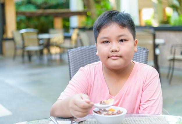Тучный толстый мальчик ест кашу с молоком
