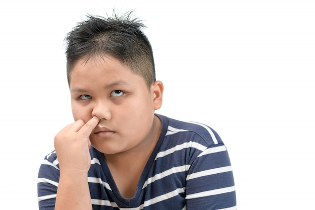 Тучный толстый мальчик ковыряется в носу и скучает изолированно
