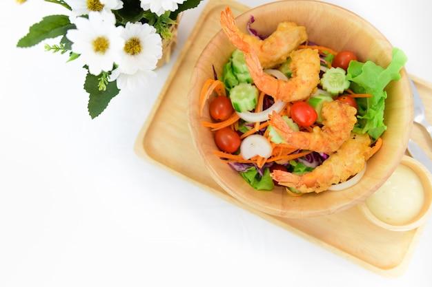 白いテーブルに揚げたエビのサラダ
