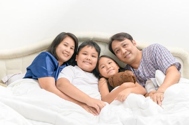 横になっている幸せなアジア家族とベッドの上の笑顔