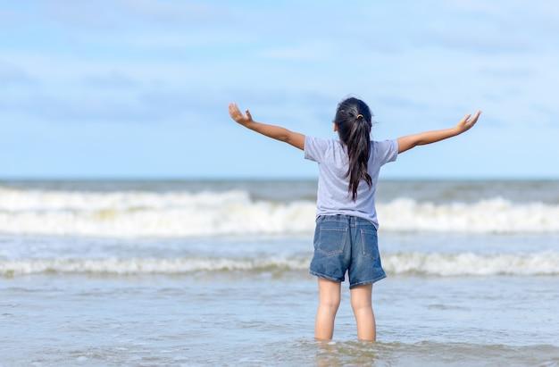 Счастливая маленькая девочка наслаждается свободой с открытыми руками на море,