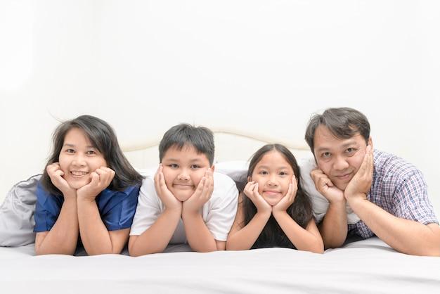 一緒にベッドで横になっているアジアの幸せな若い家族