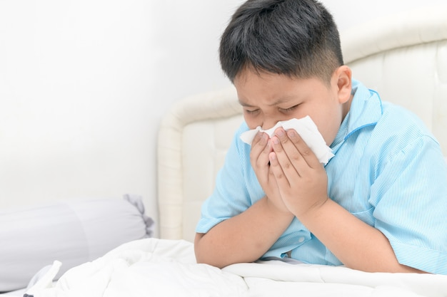 太った少年は鼻水があり、組織に鼻を吹きます