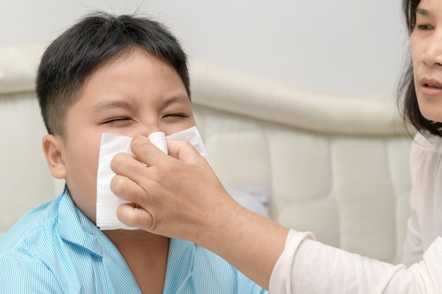Больной азиатский ребенок вытирает или чистит нос тканью
