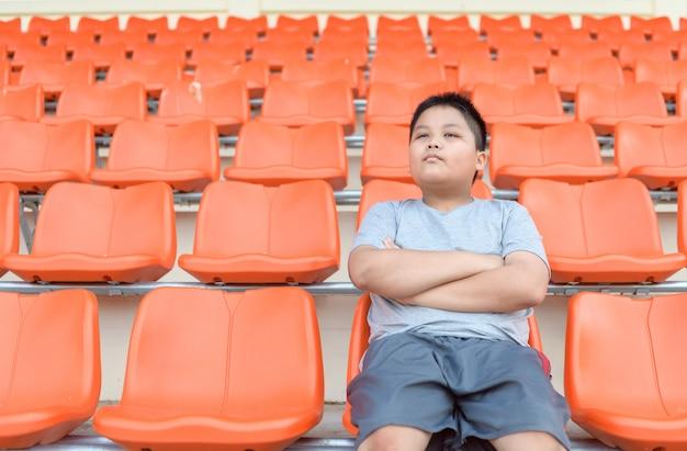 太った少年はサッカーのグランドスタンドに座っています。