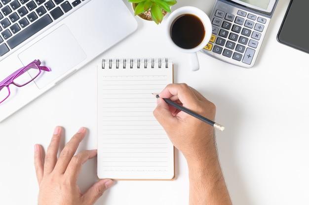 空白のノートブックに何かを書く手マンと白いオフィスデスクテーブル