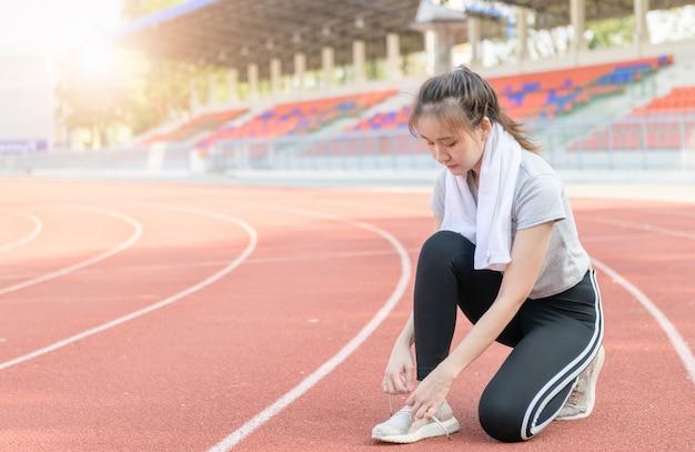 Девушка спортсмена пробуя кроссовки готовясь к бегу