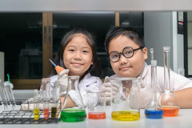 Счастливые двое детей делают научные эксперименты.