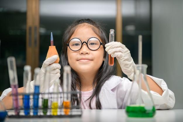 Маленький ученый использует капельницу для проведения эксперимента в химической лаборатории,