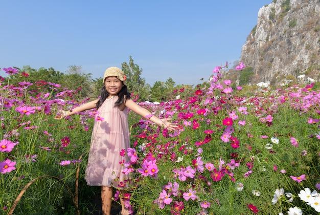 コスモスガーデンで幸せなかわいいアジアの女の子の笑顔