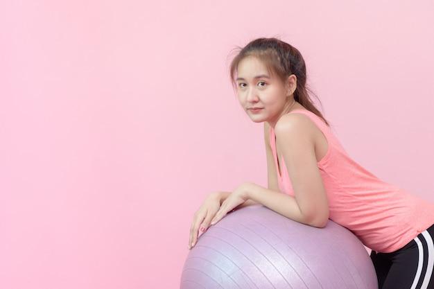 ピンクの背景のボールでかわいいアジアの女性の笑顔。