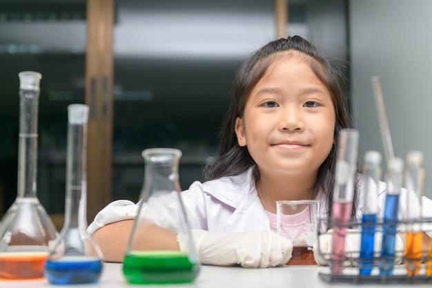 Счастливая маленькая девочка носить лабораторный халат, делая эксперимент.