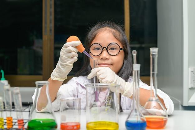 Счастливая маленькая девочка носить лабораторный халат, делая эксперимент