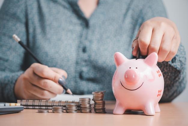 女性はピンクの貯金箱にコインを入れて、