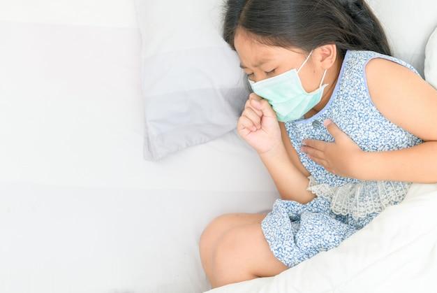 衛生的なマスクを身に着けているアジアの女の子は咳と胸の痛み、
