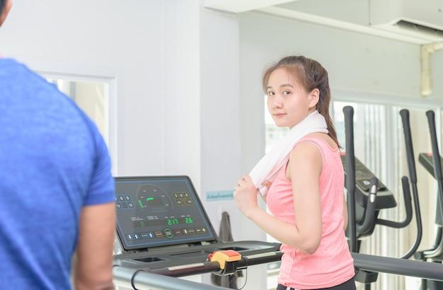 かなりアジアの女の子がジムでトレッドミルでワークアウトします。