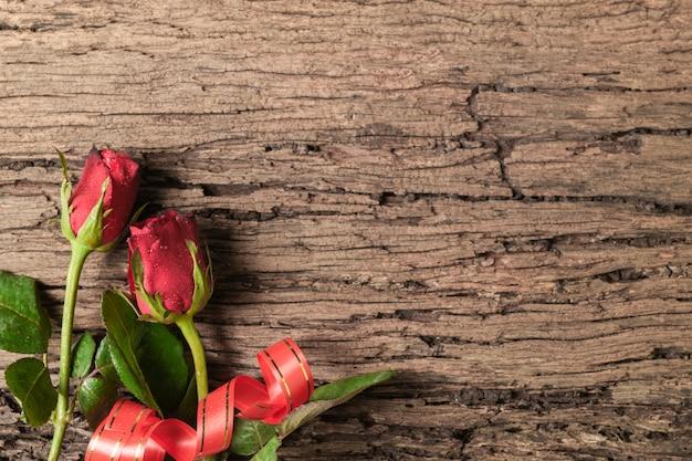 赤いバラと古い木材の背景にリボン