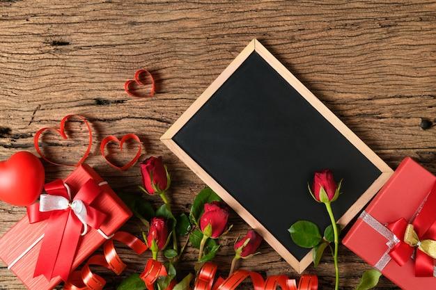 赤いバラと古い木の上のハートリボンと空の黒板