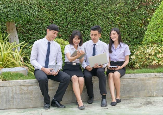 タブレットを使用して大学の宿題をするアジアの学生、