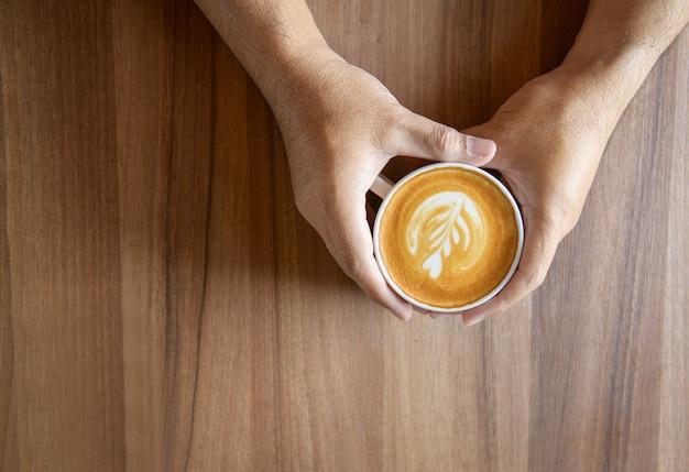 カフェラテアート。一杯のコーヒーを保持している男の手