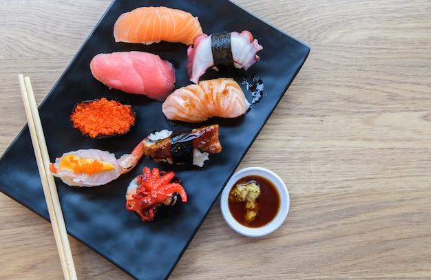にぎり寿司サーモン、ハタ、ウナギ、マグロ、エビを粘土板にのせて、