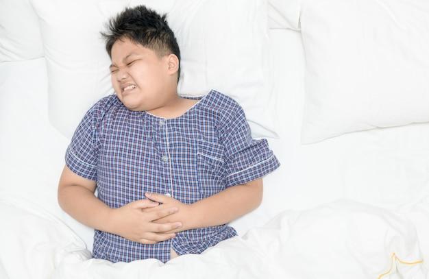 腹痛に苦しんでベッドに横になっている肥満の脂肪の少年。