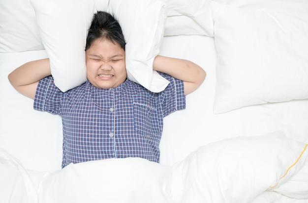 うるさいうるさい騒音のため、枕で頭を覆っている太った少年。