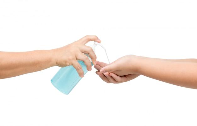 Мама рукой отжимает бутылку и наливает спиртосодержащую дезинфицирующую на руку ребенку.