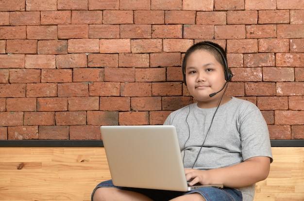 Тучный мальчик студент носить наушники учиться онлайн с учителем на дому,