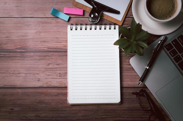 空白のノートブックと古い木の眼鏡とラップトップコンピューターのペン